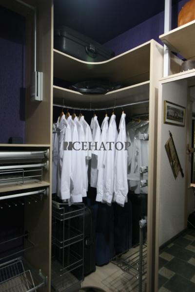 Одежда на изогнутой вешалке в гардеробе
