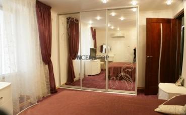 Трехстворчатый зеркальный шкаф-купе в спальне